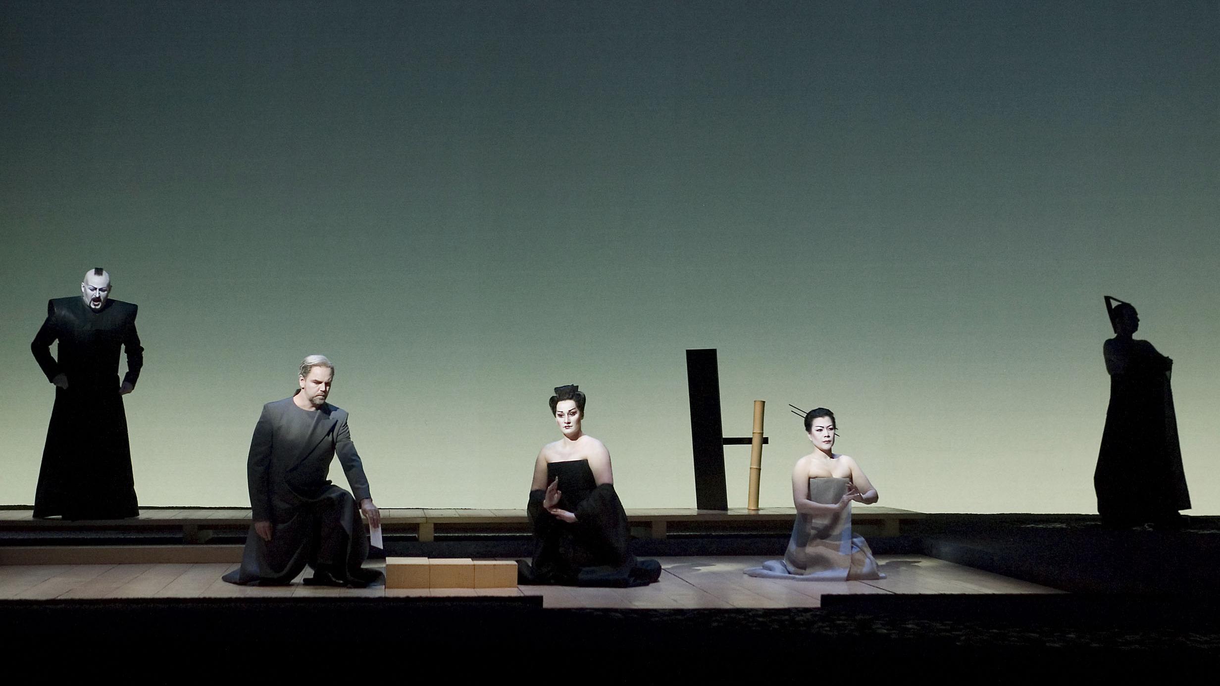 Drie mensen op hun knieën op het podium, links en rechts staan twee mensen.