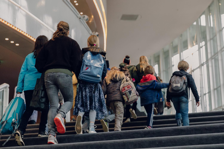 Kinderen lopen het theater binnen