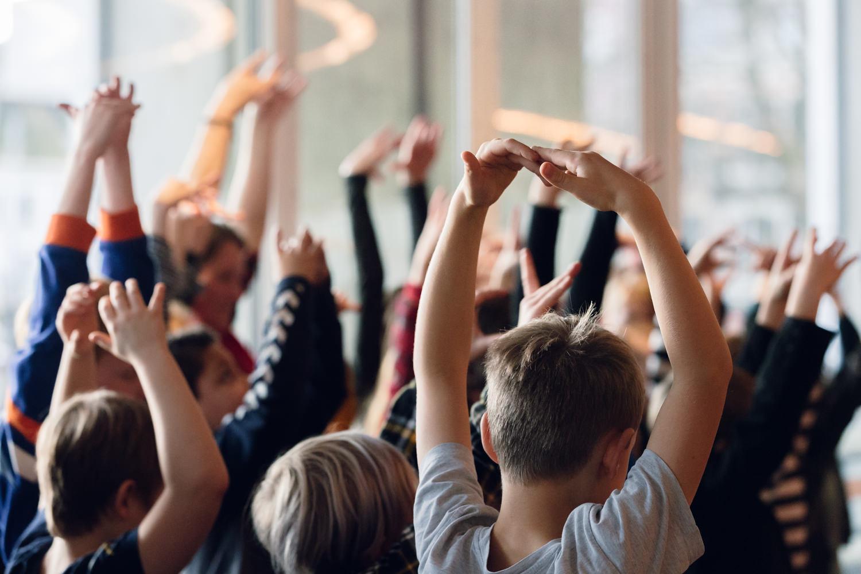 Dansende leerlingen in een aula