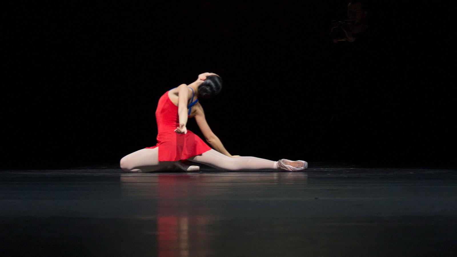 Vrouw zit op de grond, rode jurk.