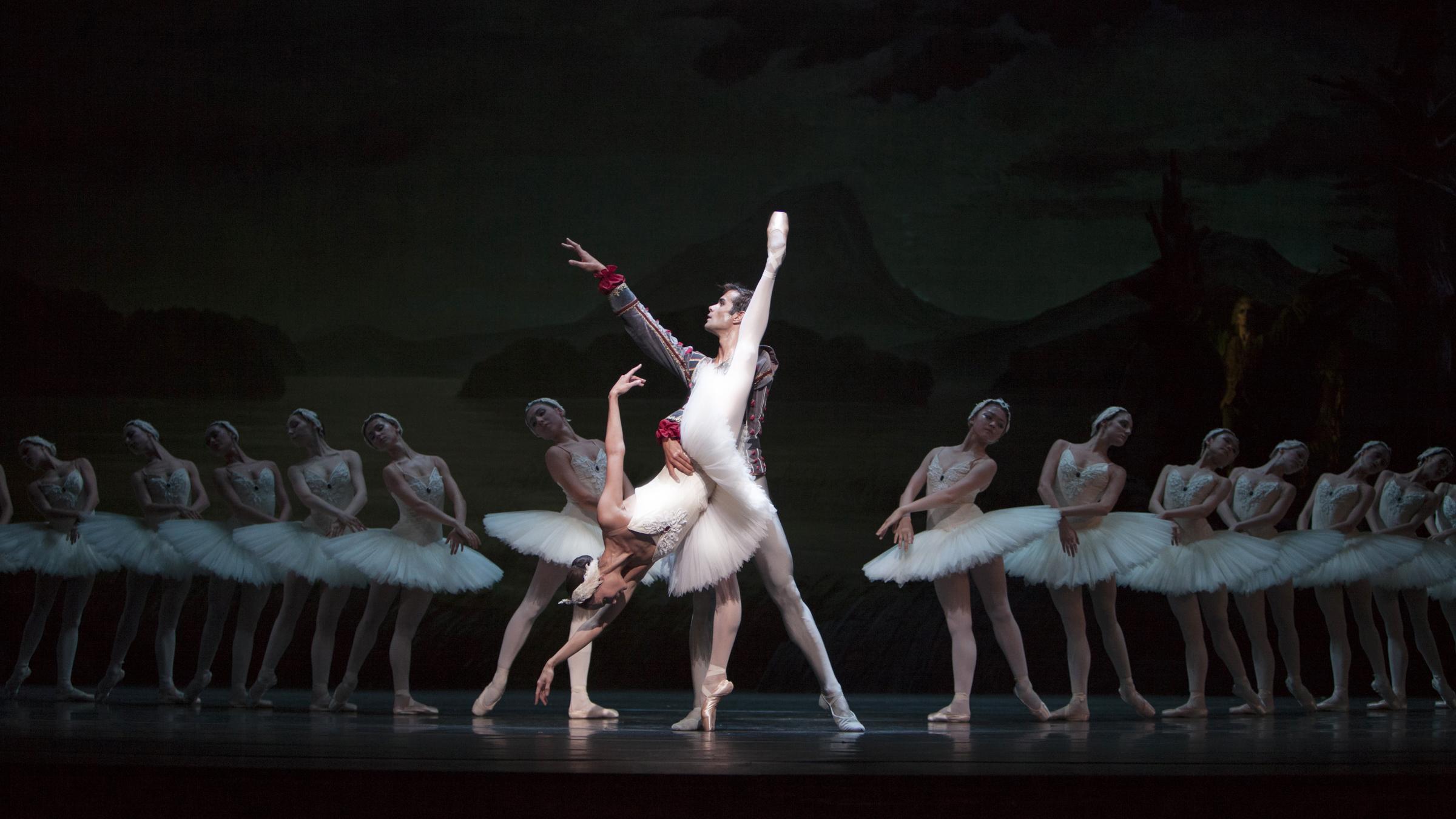 Het zwanenmeer, een man en vrouw staan in het midden, aan de zijkanten staan in het donker nog meer dansers