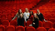 zes vrouwen bij rode stoelen